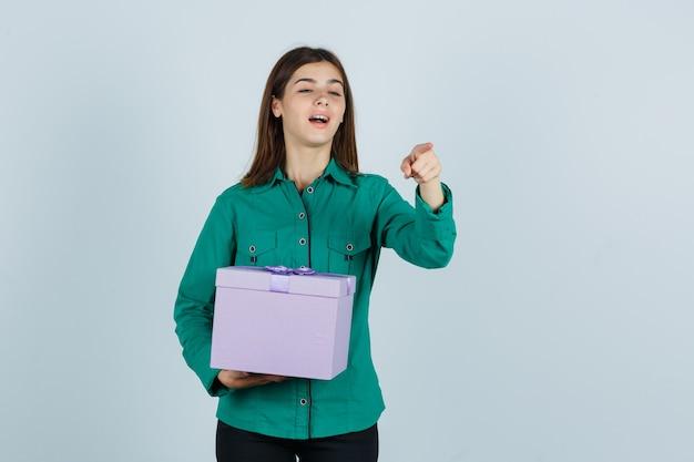 Junges mädchen in der grünen bluse, schwarze hose, die geschenkbox hält, auf kamera mit zeigefinger zeigt und fokussierte vorderansicht schaut.