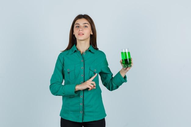 Junges mädchen in der grünen bluse, schwarze hose, die glas der grünen flüssigkeit hält, mit zeigefinger darauf zeigt und fokussierte vorderansicht schaut.