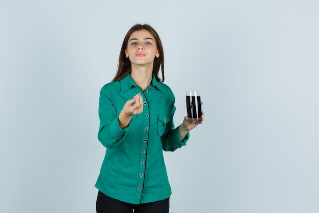 Junges mädchen in der grünen bluse, schwarze hose, die glas der schwarzen flüssigkeit hält, italienische geste zeigt und zufrieden schaut, vorderansicht.