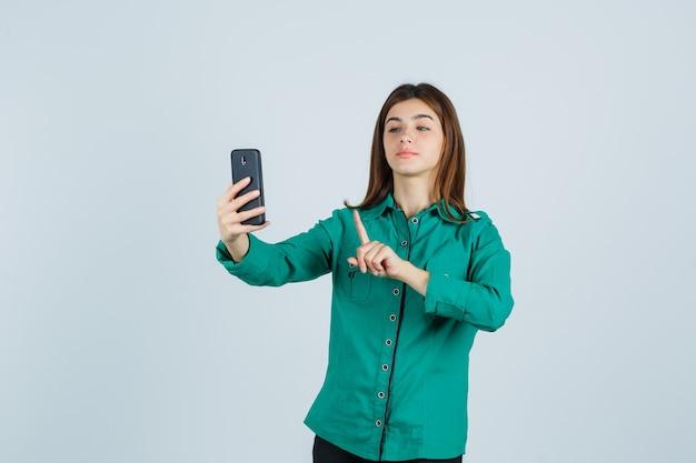 Junges mädchen in der grünen bluse, schwarze hose, die halt auf einer winzigen geste zeigt, während videoanruf macht und niedliche vorderansicht schaut.