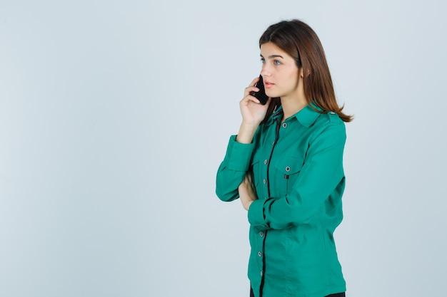 Junges mädchen in der grünen bluse, schwarze hose, die mit telefon spricht und fokussiert, vorderansicht schaut.