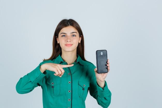 Junges mädchen in der grünen bluse, schwarze hose, die telefon in einer hand hält, darauf zeigt und fröhlich schaut, vorderansicht.