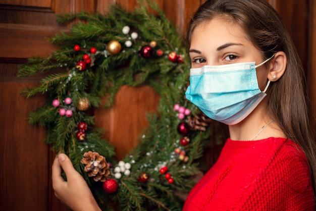 Junges mädchen in der medizinischen maske, die nahe der tür ihres hauses steht und einen selbst gemachten weihnachtskranz aufhängt
