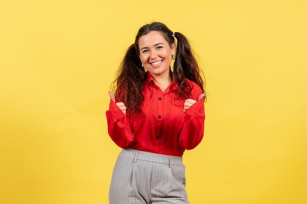 Junges mädchen in der roten bluse breit lächelnd auf gelb