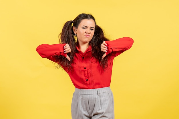 Junges mädchen in der roten bluse, die ungleiche zeichen auf gelb zeigt