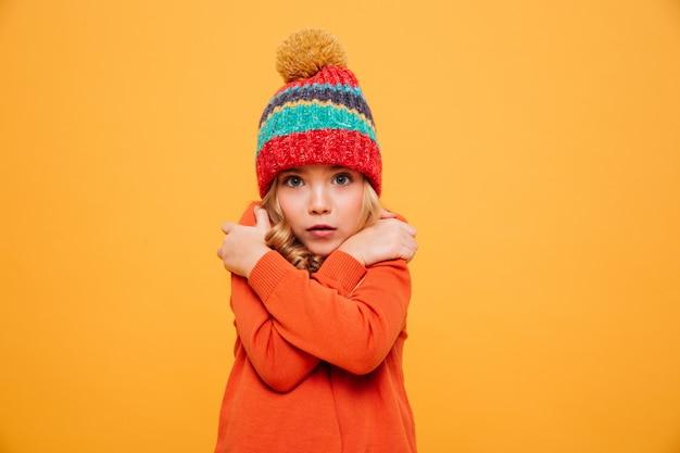 Junges mädchen in der strickjacke und in hut, die kälte haben und die kamera über orange betrachten