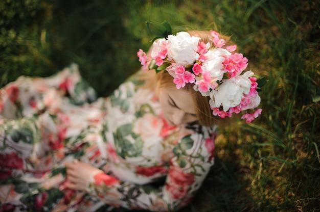Junges mädchen in einem blumendiadem, das auf dem gras sitzt