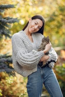 Junges mädchen in einem grauen pullover, der draußen mit einer katze aufwirft