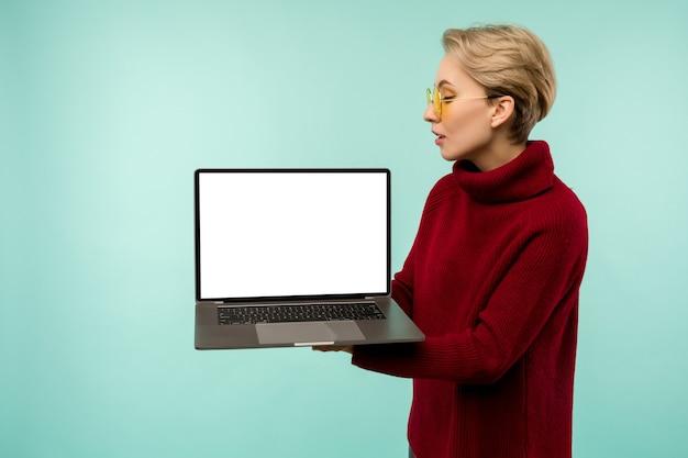 Junges mädchen in einem roten pullover demonstriert einen leeren laptop-bildschirm auf einem blauen hintergrund