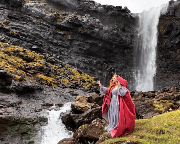 Junges mädchen in einem roten umhang bleibt in der nähe von fossa wasserfall im herbst, streymoy, färöer inseln