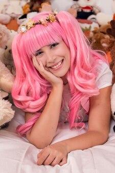 Junges mädchen in einem schlafzimmer in einem rosa netten kleid