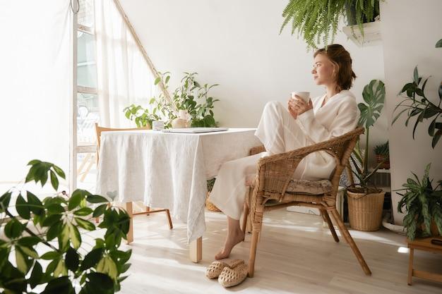 Junges mädchen in einem schönen, gemütlichen weißen musselin-pyjama, das kaffee trinkt und an sie denkt