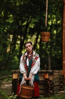 Junges mädchen in einem ukrainischen kleid wirft mit einem eimer nahe dem brunnen auf