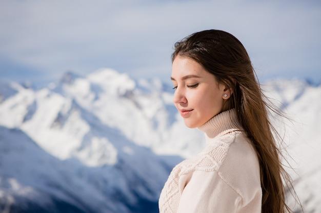 Junges mädchen in einem winteranzug, der die berge betrachtet