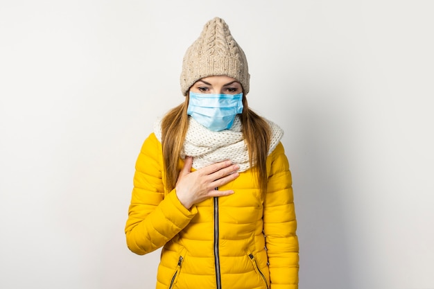 Junges mädchen in einer gelben jacke und einem hut mit einer medizinischen maske auf ihrem gesicht, die ihre hand an ihre brust hält und hustet
