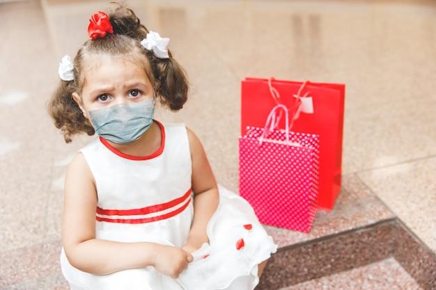 Junges mädchen in einer schutzmaske. epidemie bei kindern