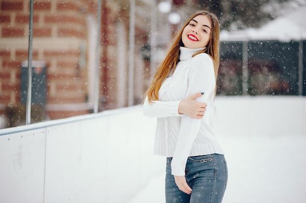 Junges mädchen in einer weißen strickjacke, die in einem winterpark steht
