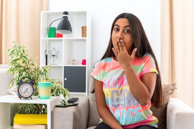 Junges mädchen in freizeitkleidung, das in schockiertem mund mit der hand auf dem stuhl im hellen wohnzimmer sitzt