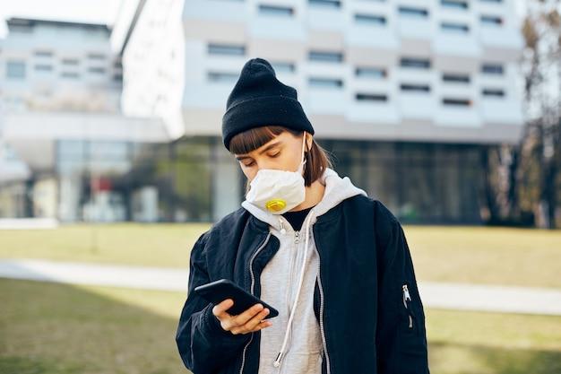 Junges mädchen in freizeitkleidung und mit atemmaske unter verwendung ihres telefons auf der straße, allein im freien in schutzmaske durch moderne architektur