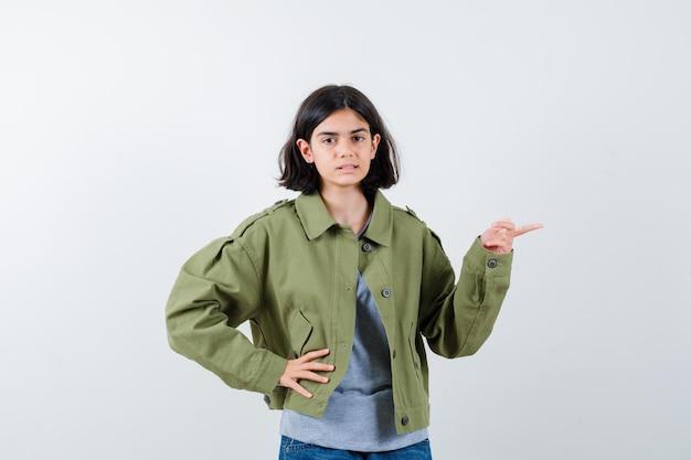 Junges mädchen in grauem pullover, khaki-jacke, jeanshose, die nach rechts zeigt, während sie die hand an der taille hält und ernst aussieht, vorderansicht.