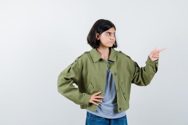 Junges mädchen in grauem pullover, khaki-jacke, jeanshose, die nach rechts zeigt, während sie die hand an der taille hält und süß aussieht, vorderansicht.