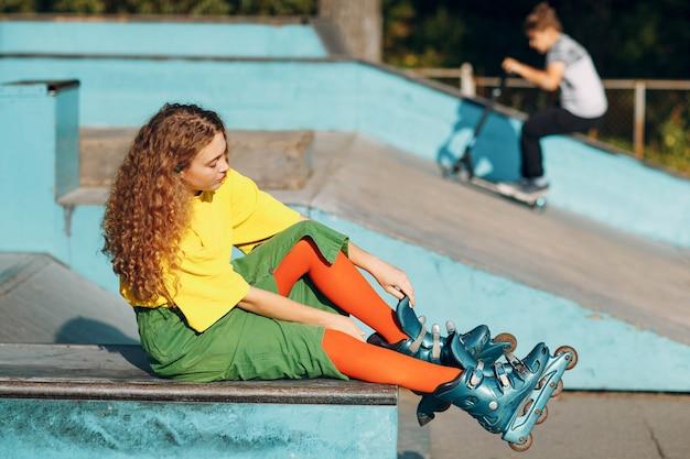 Junges mädchen in grüner und gelber kleidung und orangefarbenen strümpfen mit lockiger frisur rollschuhlaufen im skatepark