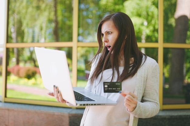 Junges mädchen in heller freizeitkleidung, die kreditkarte hält. frau, die an moderner laptop-computer in der nähe von spiegelgebäude mit baumreflexion in der straße im freien arbeitet. mobiles büro. freiberufliches geschäftskonzept.