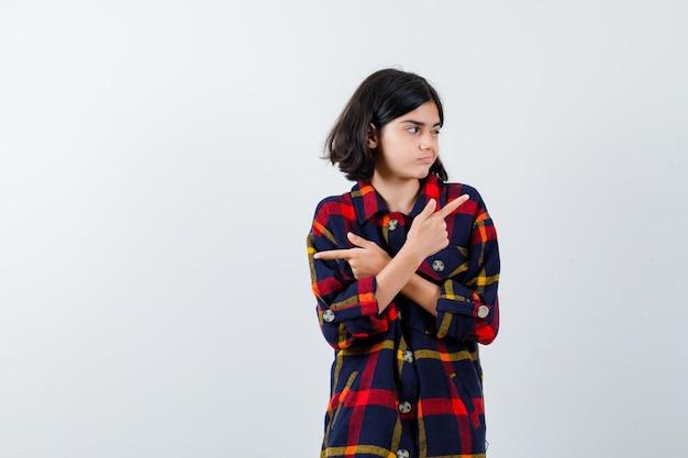 Junges mädchen in kariertem hemd, das mit den zeigefingern in entgegengesetzte richtungen zeigt und süß aussieht, vorderansicht.