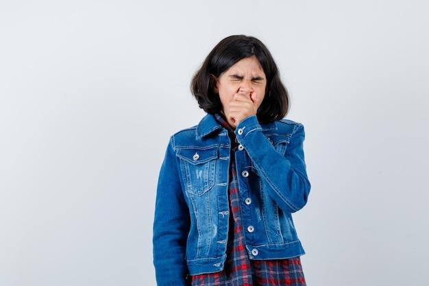 Junges mädchen in kariertem hemd und jeansjacke, die den mund mit der hand bedeckt, gähnt und müde aussieht