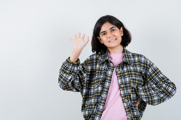 Junges mädchen in kariertem hemd und rosa t-shirt, das die hand ausstreckt, um jemanden zu begrüßen, während es die hand an der taille hält und süß aussieht looking