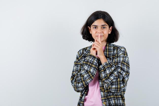 Junges mädchen in kariertem hemd und rosa t-shirt, das stillegeste zeigt und schüchtern aussieht, vorderansicht.