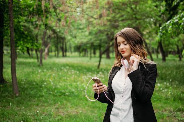 Junges mädchen in kopfhörern und mit einem smartphone