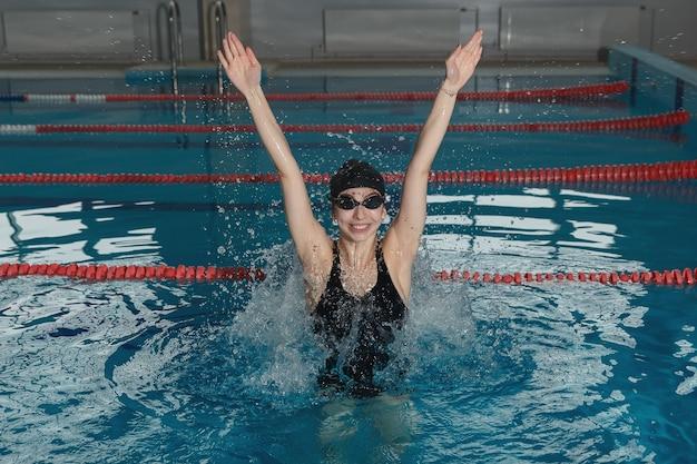 Junges mädchen in schutzbrille und mütze im schwimmbad springen.