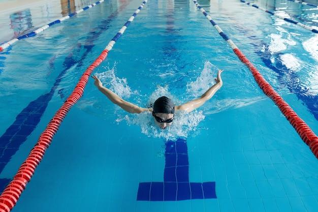 Junges mädchen in schutzbrille und mütze schwimmen schmetterlingsstil im blauen wasserpool