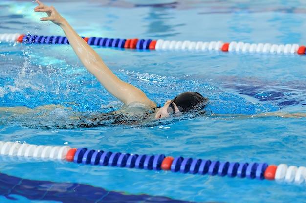 Junges mädchen in schutzbrillen und mütze schwimmen im frontkraul-stroke-stil im blauen wasserpool.