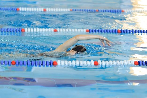 Junges mädchen in schutzbrillen und mütze schwimmen im vorderen crawl-stroke-stil im blauen wasserpool.