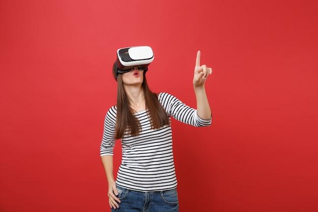 Junges mädchen in virtual-reality-brille berührt so etwas wie den knopfdruck, der auf den schwebenden virtuellen bildschirm zeigt, der auf rotem hintergrund isoliert ist. menschen aufrichtige emotionen lifestyle-konzept. kopieren sie platz.