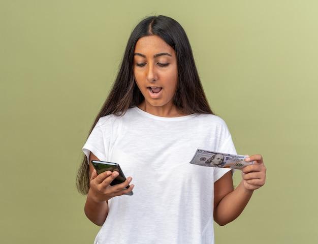 Junges mädchen in weißem t-shirt, das bargeld hält und auf den bildschirm ihres smartphones blickt