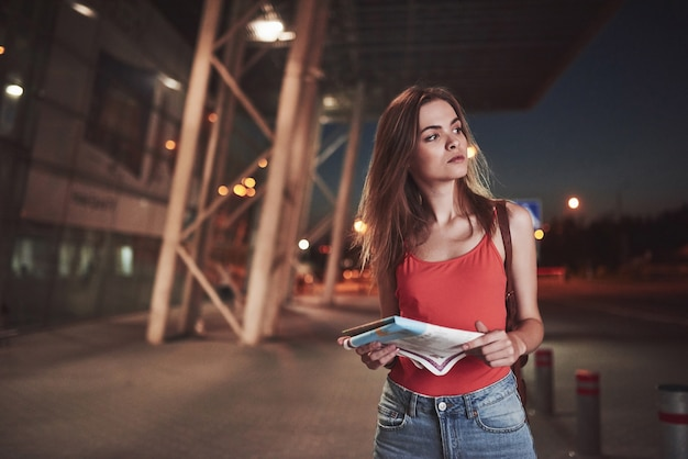Junges mädchen kostet nachts in der nähe des terminals des flughafens oder bahnhofs und liest stadtplan