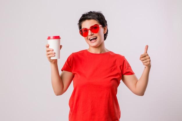 Junges mädchen lächelnd mit einem glas kaffee auf weiß