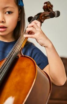 Junges mädchen lernt, wie man zu hause cello spielt
