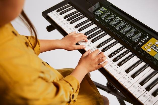 Junges mädchen lernt, wie man zu hause elektronische tastatur spielt
