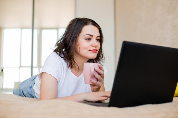 Junges mädchen liegt zu hause auf einem bett mit kaffee und einem laptop
