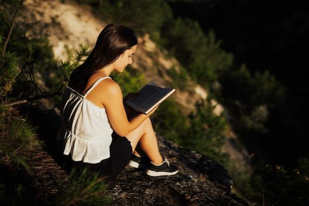 Junges mädchen liest buch, während gegen schöne naturlandschaft sitzt.