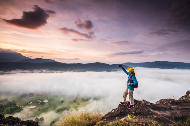 Junges mädchen machen fotos das nebelmeer auf hohem berg.