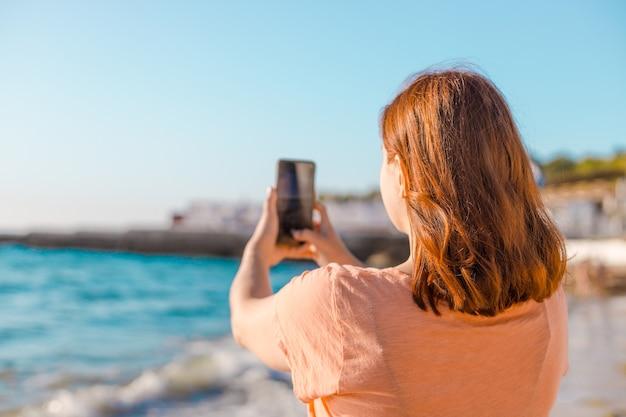 Junges mädchen macht ein foto des meeres oder des ozeans am ufer am sonnigen tag.