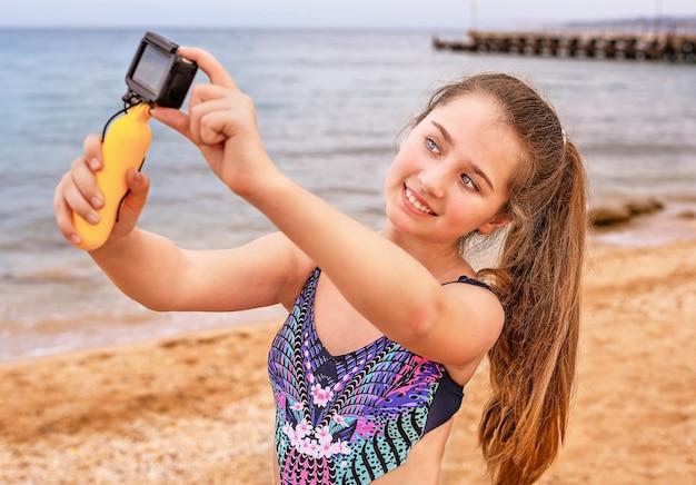 Junges mädchen macht selfie und video am strand.