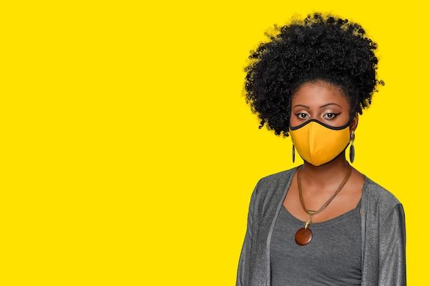 Junges mädchen mit afrostylem haar, das eine covid19-isolierte coronavirus-schutzmaske auf gelbem rücken trägt