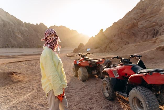 Junges mädchen mit bedecktem gesicht, das sich auf eine wüstensafari auf atvs vorbereitet