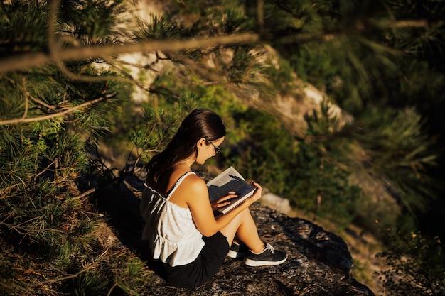 Junges mädchen mit brille, die auf dem felsen im berg sitzt und ein buch während des ruhigen sonnigen sommertages liest, voll des warmen lichts.